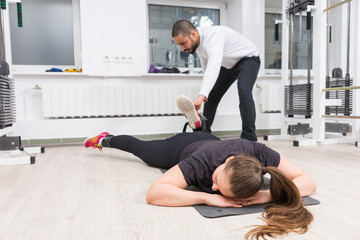 Personal trainer assisting woman at gym