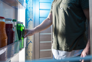 Man selecting a bottle of beverage from his fridge