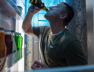 Thirsty man drinking a cold beer at home