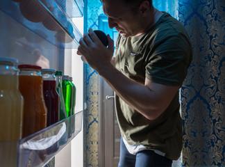 Man searching inside his fridge at night
