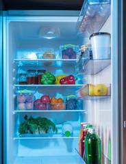 Open fridge with healthy fresh food inside