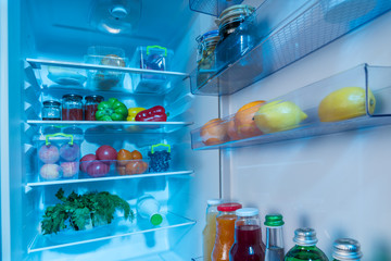 Open interior of a fridge packed with fresh food