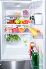 Open fridge with fresh fruit and vegetables