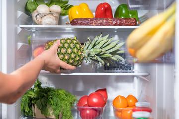 Man putting fresh pineapple into fridge
