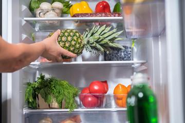 Person putting fresh pineapple into fridge