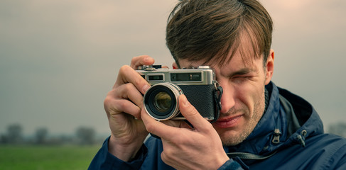 photographer shoots an analog camera in nature. Web banner.