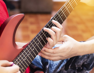 Father hands his son to play red guitar.