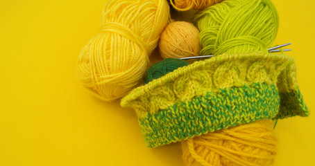Yellow and green coats of wool lie on the table. Favorite hobby is knitting.