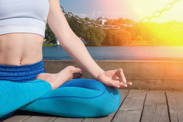 Young pretty woman practices yoga and meditates on the sunny embankment of the river
