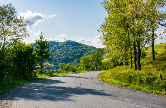 country road down the hill. forest along the way and mountain in the distance. wonderful sunny weather in early autumn