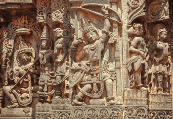 South Indian temple relief with hero Arjuna with bow and arrows in hands. Hindu structure from 12th century, Halebidu, India