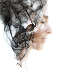 Double exposure portrait of a young woman and a smoky texture dissolving into her hair and face
