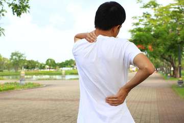 Close up of Man with shoulder pain or neck pain in the public park,Health concept