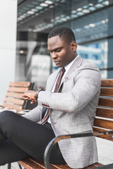 black man businessman in a business suit, expensive watch and glasses sitting on a bench and talking on the phone against the backdrop of a modern city