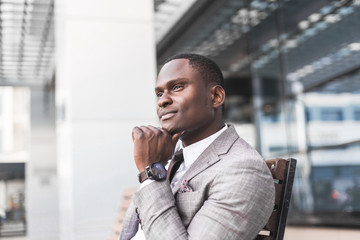black man businessman in a business suit, expensive watch and glasses sitting on a bench against the backdrop of a modern city