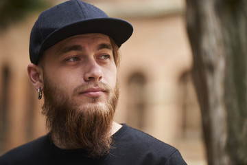 Portrait of Handsome bearded man with piercing in black cap