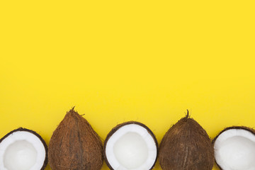 Tropical summer coconut background. half and whole coconuts on a yellow background