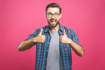 Portrait of young man in glasses showing thumbs up isolated over pink background