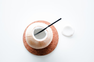 Young open coconut on white table. Copy space