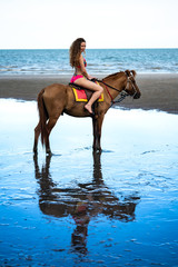 Young beautiful woman riding horse on seacoast