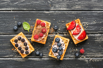 Waffles with fresh berries and fruits on a rustic wooden background. Homemade waffles with a variety of fillings. Flat lay, view from above.