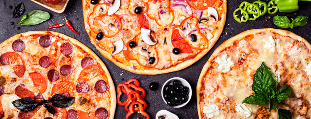 selection of different pizzas on a black background and ingredients. Peperoni, Vegetarian and Seafood Pizza