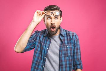 OMG! It's incredible! Portrait of handsome young man in glasses looking at camera while standing against pink background. Close up portrait of bearded man keeping his mouth open.