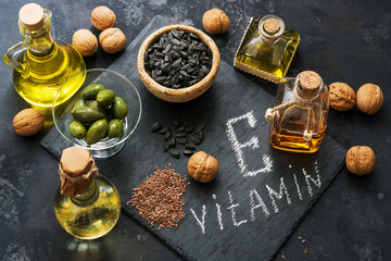 Food rich in vitamin E. A set of different oils. Seeds of flax, sunflower, walnut, olives. Top view.