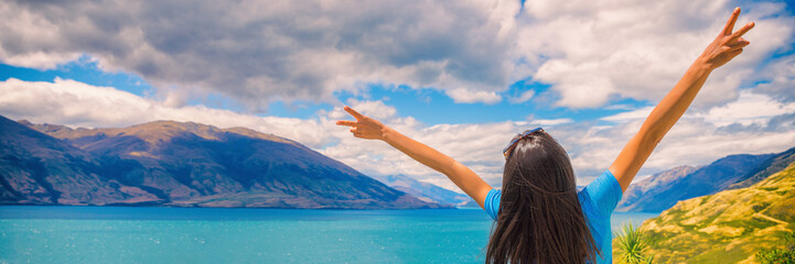 Travel adventure fun tourist girl wanderlust lifestyle banner panorama. New Zealand vacation summer tourism destination woman happy with arms up doing peace sign .