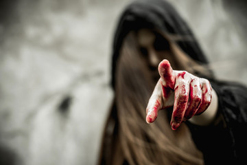 Asian woman dress black as Grim Reaper of death and point the finger at you in Halloween festival. Halloween concept.