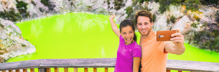New Zealand tourism travel destination people lifestyle. Banner panorama. Couple tourists taking selfie travel destination, Waiotapu. Active geothermal green pond, Rotorua, north island, Wai-O-Tapu.