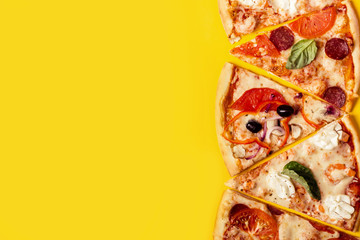 selection of Assorted pieces pizza on yellow background. Pepperoni, Vegetarian and Seafood Pizza