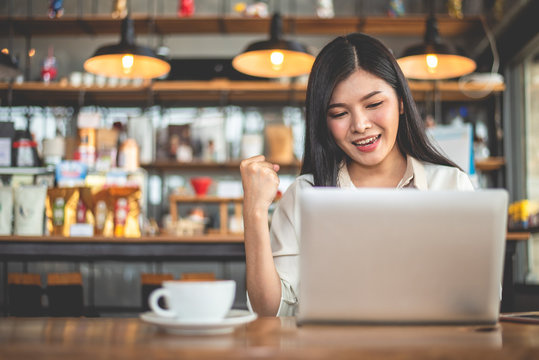 Asian female freelancer doing happy gesture by raising hand when using laptop in cafe. Business and success concept. Coffee shop and outdoors theme. Cafeteria background.