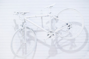 White bicycle hanging on white wall