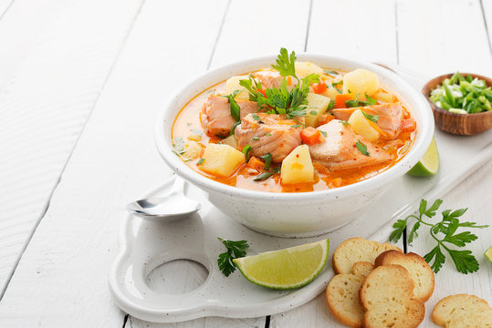 Salmon soup with cream, potatoes, carrots and parsley on white background.