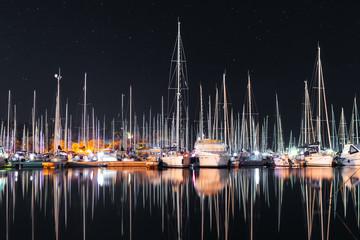 Many yachts sail boats in marina bay at night mirroring in a sea