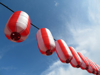 Red-white japanese paper lanterns Chochin against blue sky with white clouds. Traditional festive decoration in Japan