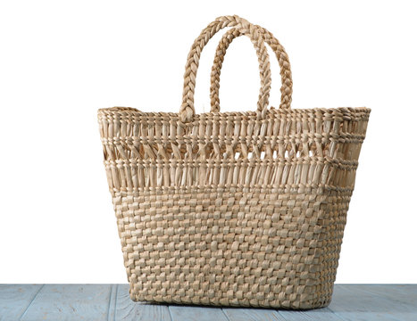Straw bag on the table with isolated background