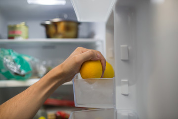 the man is eating lemon on the background of an open refrigerator