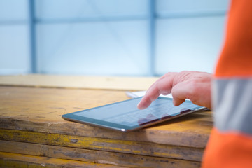 Male engineer using digital tablet at construction site, only hand and part of body in orange safety jacket visible with space for your copy text