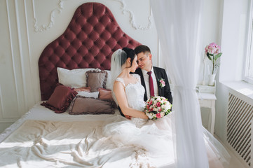 Beautiful newlyweds lie on a bed in a stylish studio and hug. Wedding portrait of a young groom and a sweet bride.