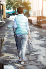 Young cute woman in blue jacket with bag is walking along the street full length.