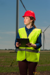 Portrait of a ambitious successful young female engineer in a green vest and red hard hat designing a plan against a background of windmills