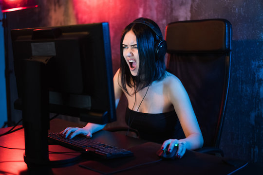 Screaming emotional young angry woman playing on personal computer holding game keyboard and mouse sitting on a chair at home. Gaming gamers concept.