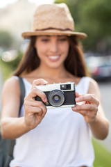 attractive young woman taking pictures outdoors