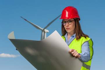 Serious young female engineer in red helmet and glasses with projects and plans against the background of a windmill and blue sky