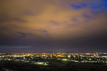 Wide panorama, aerial night view of modern tourist Ivano-Frankivsk city, Ukraine. Scene of bright lights of tall buildings, high television tower and green suburbs on evening cloudy sky background.