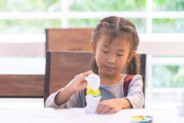 Asian girl is painting a doll in Art classroom.