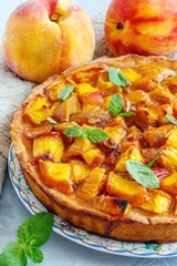 Open pie with peaches and fresh mint.