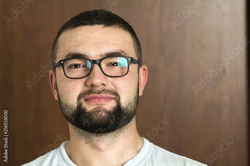 99cb3070eb90 Portrait of handsome bearded black haired intelligent modern young man in  glasses with short haircut and